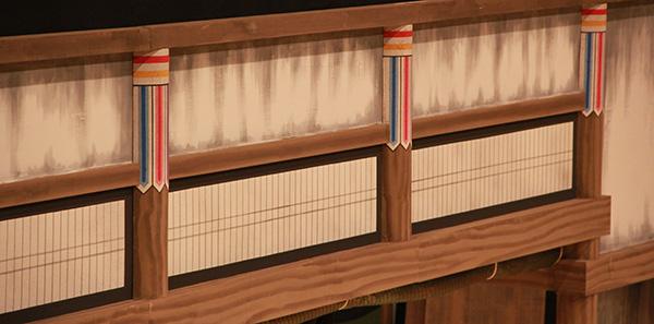 『天一坊』の二幕目「本堂の場」。全体的に地味な色味の場面ですが、柱の上の方を見ると、ちょっとカラフルな部分があります。これは「剣垂(けんだれ)」と呼んでいます。