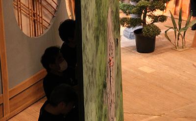 『天保遊俠録(てんぽうゆうきょうろく)』の道具調べの様子です。下手側には、BGMを担当する黒御簾(くろみす)の部屋がありますが、中の演奏者が舞台や花道を見るための窓があります。黒御簾を囲う絵に、その窓のための穴をあけているところです!