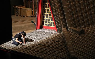 『南総里見八犬伝』の大屋根です。屋根での立ち回りの後、どーんと屋根が倒れる「がんどう返し」という大仕掛けになります。 写真は、その大屋根の瓦の手直しをしている塗方です。お客様からは見えにくいところなのですが、丁寧にそして手早く筆を走らせていました。 照明テストの時間帯に、ちょっとドラマティックに光が当たっていたので、その瞬間をパチリ。