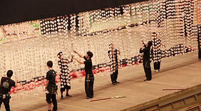 舞台の上には、いろいろなものを吊っていますが、次の公演に向けて、吊り替えなども行います。写真は、糸桜(桜の造花のカーテンみたいなもの)をいったんおろして、引き上げているところ。長いのでからまらないように、ぼぐしております。