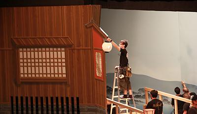 『祇園恋づくし』の四条河原。料亭の提灯を取り付けているところです。この白い提灯には、京都の南座の川向かいにある料亭の名前が書かれています。