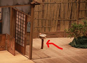 『文七元結』の長兵衛さんの家の庭。赤い矢印の台が「くもで」です。ちなみに、上にのっている白い手水鉢は小道具です。