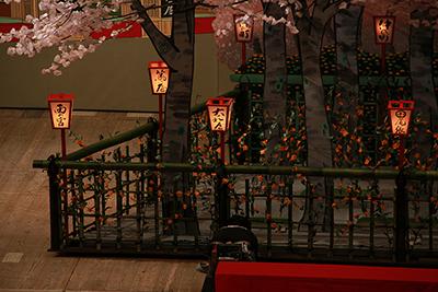 『御所五郎蔵』序幕の五條坂廓の場面。舞台が明るいと気づかれない方もいらっしゃるかもしれませんが、桜の木のそばにあるぼんぼりには、灯りがともっています。 灯りがわかりやすいように、舞台が暗くなったときを狙って、撮影してみました。