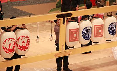 『江戸花成田面影』で舞台上方に飾られる提灯です。提灯に描かれているのは、成田屋さんの紋の三升、杏葉牡丹、そして歌舞伎座の劇場の紋の鳳凰丸です。