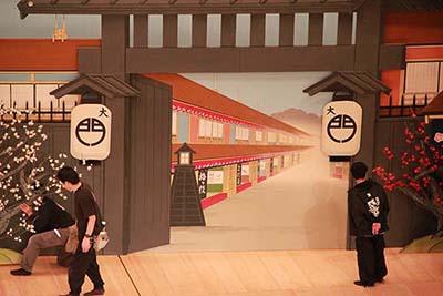『女戻駕(おんなもどりかご)』の舞台です。江戸吉原の大門。どこまでが平面で、どこが立体なのか。舞台に飾るとなんとも不思議な感じで、おもしろいです。