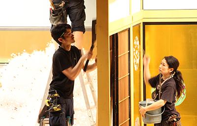 『嫗山姥』。左でのこぎりを持っているのは製作課、右でバケツを抱えて色の仕上げをしているのは塗方(ぬりかた)と呼ばれる第二美術課のメンバーです。製作課、第二美術課は普段は千葉県の松戸で仕事をしていますが、初日前には歌舞伎座に詰め、舞台で仕上げなどをやっています。
