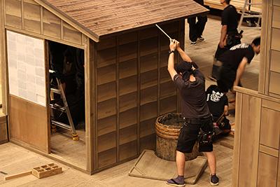 『らくだ』の屋体を大工チーム(製作課)が調整しているところです。古そうな井戸もありますが、これも大道具です。